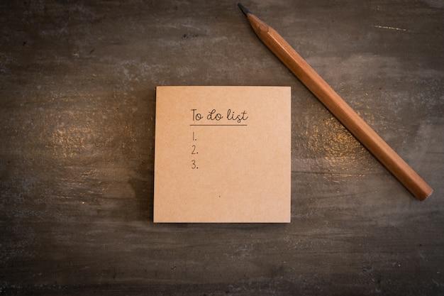 Vue de dessus de la liste des tâches sur le post it patper avec un crayon sur la table vintage.