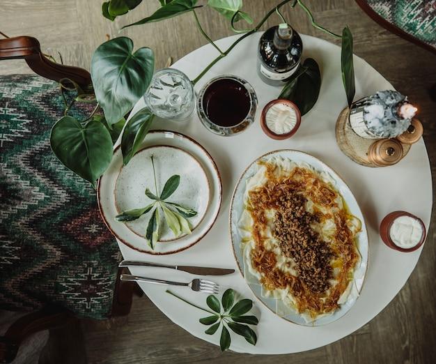 Vue de dessus de la liste traditionnelle azerbaïdjanaise khingal dans l'assiette avec du yaourt aigre dans des pots en argile sur un tableau blanc