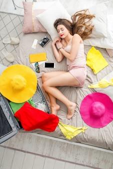 Vue de dessus sur le lit avec une jeune femme, des vêtements différents et des trucs pour les vacances d'été. rêver du concept de voyage d'été