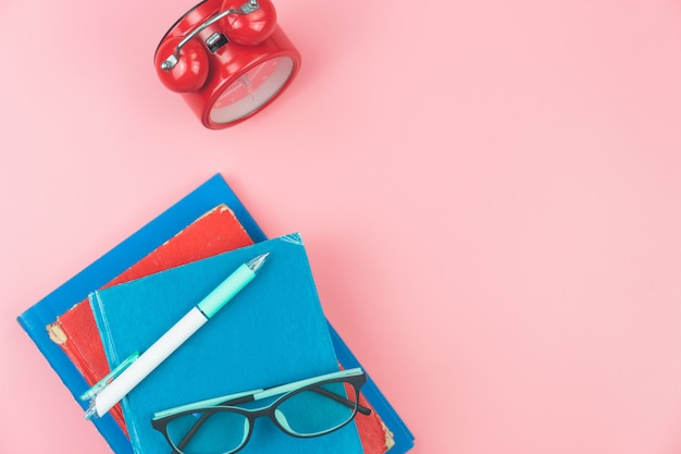 Vue de dessus avec des livres, des lunettes, stylo horloges frais généraux sur fond pastel rose, plat laïque éducation