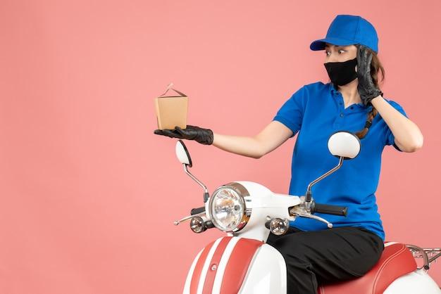 Vue de dessus d'un livreur surpris portant un masque médical et des gants assis sur un scooter livrant des commandes sur une pêche pastel