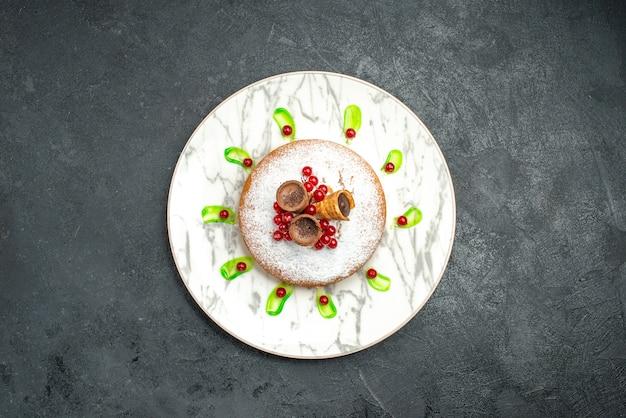 Vue de dessus de loin une assiette à gâteau d'un gâteau appétissant avec des baies de gaufres au sucre en poudre