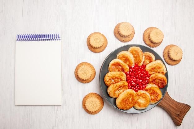 Vue de dessus de loin assiette sur la planche de biscuits et assiette de crêpes appétissantes et de grenade sur la planche à découper en bois à côté du cahier blanc sur la table