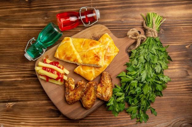 Vue de dessus de loin aux herbes de restauration rapide tarte au poulet frites sur la planche à découper à côté des bouteilles et des herbes