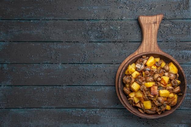 Vue de dessus de loin bol de nourriture bol en bois de pommes de terre aux champignons sur la planche à découper sur le côté droit de la table