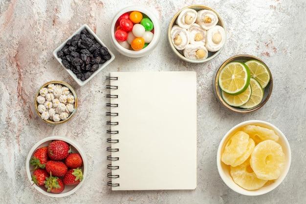 Vue de dessus de loin des bols d'agrumes de bonbons aux baies et d'ananas séchés sont disposés en cercle à côté du cahier blanc
