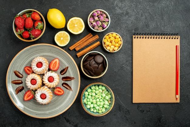 Vue de dessus de loin des bonbons avec des biscuits au thé avec du thé noir à la fraise avec des noisettes de citron des bols de chocolat et différents bonbons à côté d'un cahier à la crème et d'un crayon rouge sur une surface sombre