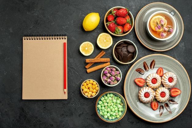 Vue de dessus de loin des bonbons avec des biscuits au thé avec du thé noir à la fraise avec des noisettes de citron des bols de chocolat et différents bonbons à côté d'un cahier à la crème et d'un crayon rouge sur une table sombre