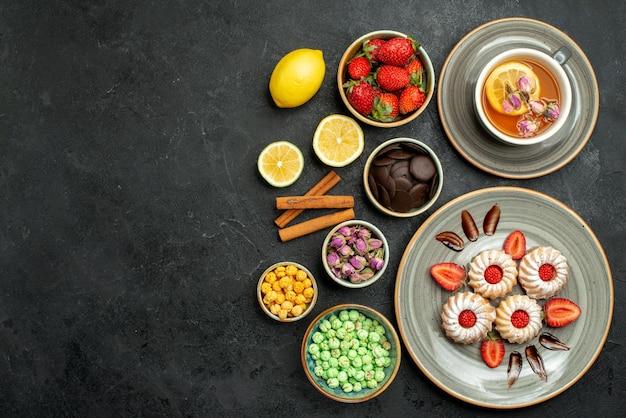 Vue de dessus de loin des bonbons avec des biscuits au thé avec du thé noir à la fraise avec des noisettes de citron des bols de chocolat et différents bonbons sur le côté droit de la table
