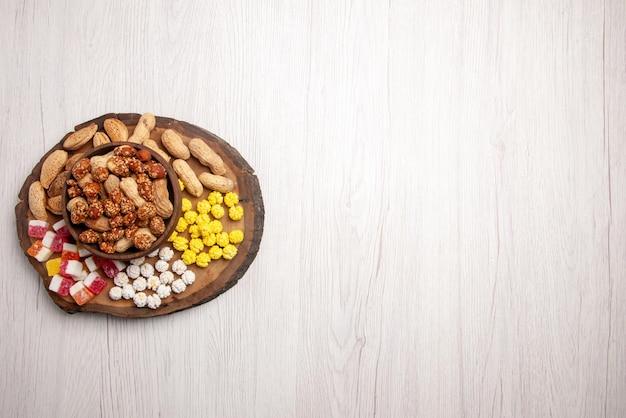 Vue de dessus de loin des bonbons dans un bol de noix sucrées dans un bol à côté des bonbons sur la planche à découper sur le côté gauche de la table blanche