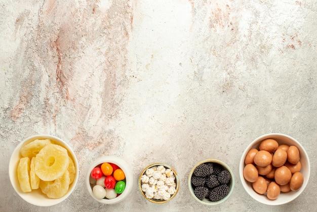 Vue de dessus de loin des bonbons dans des bols des bonbons et des ananas séchés dans des bols sur fond clair