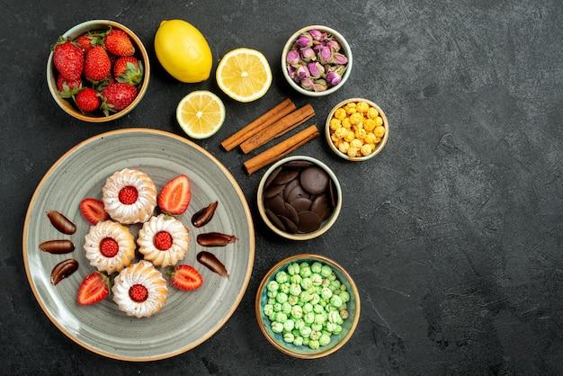 Vue de dessus de loin des bonbons avec du thé des biscuits appétissants avec du thé noir à la fraise avec des noisettes de citron des bols de chocolat et différents bonbons sur le côté gauche de la table