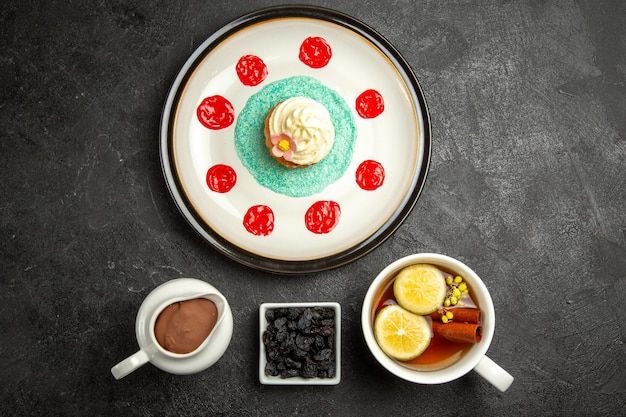 Vue de dessus de loin des bonbons avec un petit gâteau au thé avec de la crème une tasse de tisane au citron à côté du bol de crème au chocolat sur la table sombre