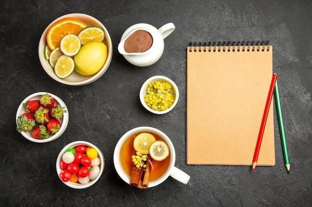 Vue de dessus de loin des bonbons sur la table une tasse de thé avec des bâtons de citron et de cannelle à côté du cahier crème avec un crayon vert et rouge et des bols de baies et d'herbes