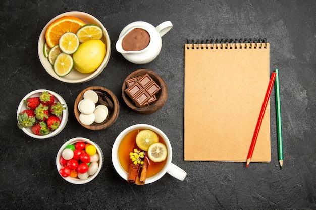 Vue de dessus de loin des bonbons sur la table une tasse de thé à la cannelle et au citron à côté du cahier crème avec un crayon vert et rouge et des bols de fraises chocolat et bonbons