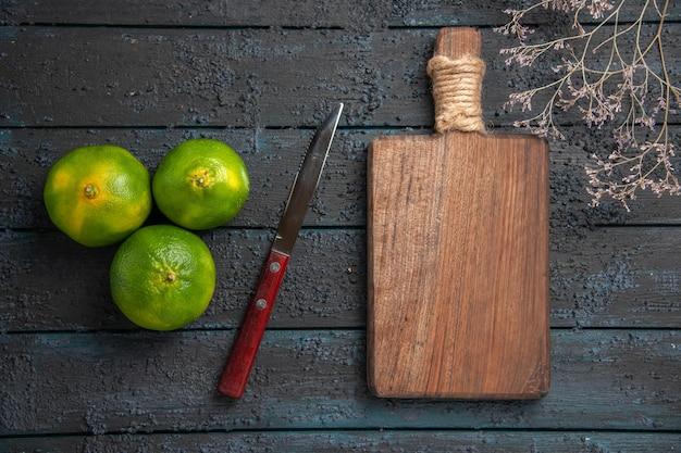 Vue de dessus de loin branches et citrons verts trois citrons verts sur la table à côté d'une planche à découper en bois de couteau et de branches d'arbres
