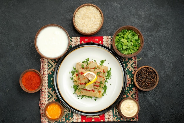 Vue de dessus de loin chou farci chou farci et bols d'herbes sauces blanches et jaunes poivre noir épices riz et crème sure sur nappe à carreaux multicolores sur surface sombre
