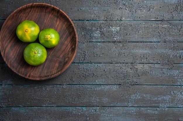 Vue de dessus de loin des citrons verts sur une assiette de trois citrons verts sur le côté gauche de la table sombre