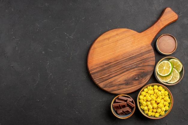 Vue de dessus de loin citrons verts et bonbons bols de différents bonbons tranches de citron vert à côté de la planche à découper sur la table noire