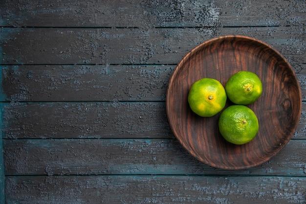 Vue de dessus de loin des citrons verts dans un bol bol marron en bois de citrons verts sur le côté droit de la table grise