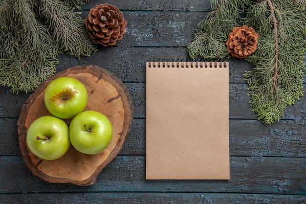 Vue de dessus de loin des cônes de cahier de pommes trois pommes vertes sur une planche à découper et un cahier crème entre des branches d'arbres avec des cônes