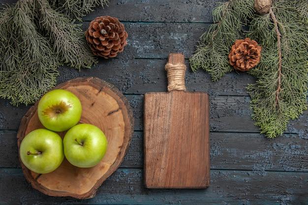 Vue de dessus de loin des cônes de pommes trois pommes vertes sur une planche à découper et une planche de cuisine en bois entre des branches d'arbres avec des cônes