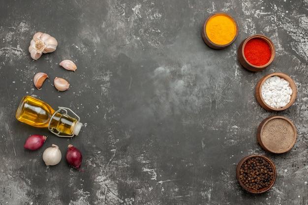 Vue de dessus de loin épices épices colorées oignon ail bouteille d'huile