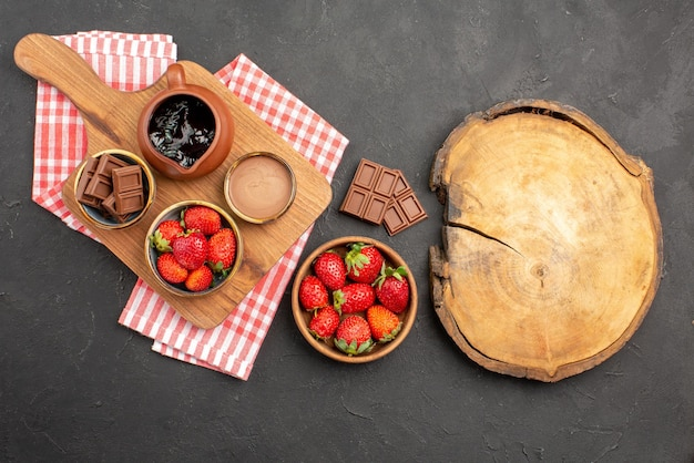 Vue de dessus de loin fraises et fraises au chocolat crème au chocolat dans un bol sur la planche à découper sur une nappe à côté de l'assiette de fraises et de la planche à découper