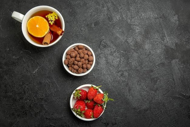 Vue de dessus de loin fraises noisettes bols bruns de fraises noisettes et une tasse de thé au citron sur la table sombre