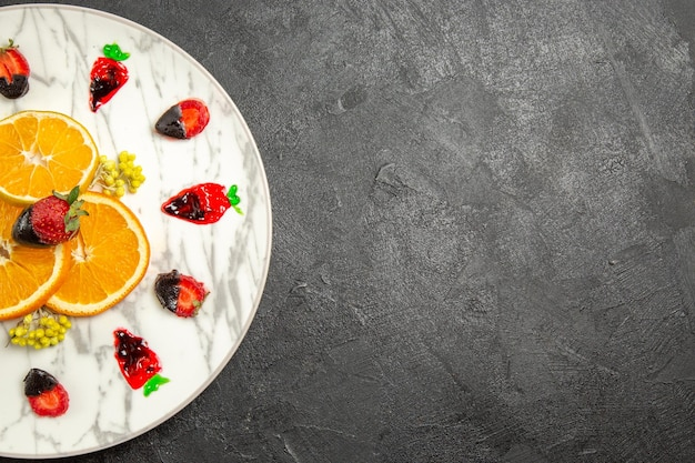 Vue de dessus de loin fruits sur l'assiette assiette de tranches d'agrumes et de fraises enrobées de chocolat sur la table noire