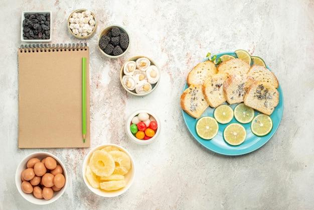 Vue de dessus de loin gâteau au citron sept bols de bonbons à côté du cahier crème avec crayon vert assiette de morceaux de gâteau au citron sur la table
