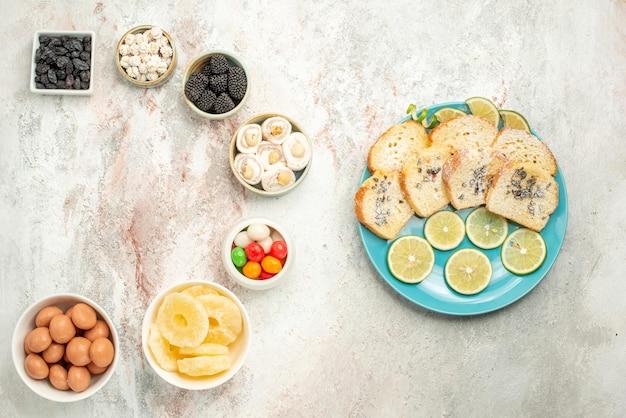 Vue de dessus de loin gâteau au citron sept bols de bonbons sur la gauche et assiette de morceaux de gâteau au citron sur le côté droit de la table