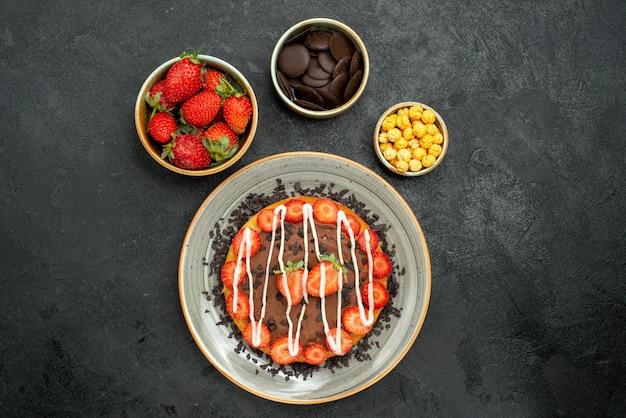 Vue de dessus de loin gâteau avec bols au chocolat de fraise noisette et chocolat et gâteau au chocolat et fraise sur table sombre