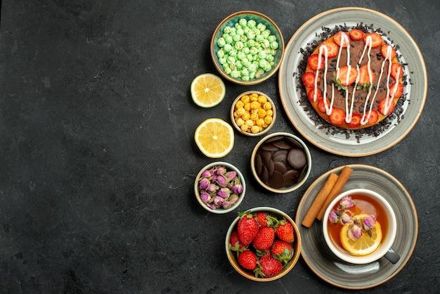 Vue de dessus de loin gâteau avec des bonbons gâteau avec du thé noir aux fraises avec des noisettes au citron des bols de chocolat et différents bonbons sur le côté droit de la table sombre