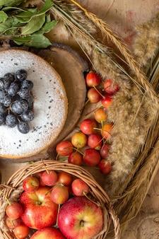 Vue de dessus de loin un gâteau un panier de gâteau de pommes sauce au chocolat baies raisins secs épillets