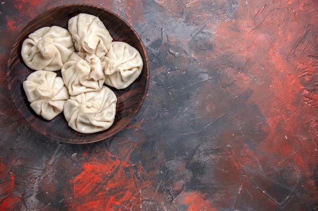 Vue de dessus de loin khinkali l'appétissant khinkali dans le bol sur la table rouge-gris