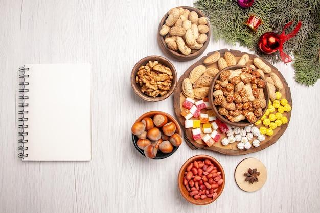 Vue de dessus de loin noix sur le plateau branches d'épicéa avec différents bonbons et cacahuètes sur le plateau de la cuisine à côté du cahier blanc bols de noisettes noix sur la table