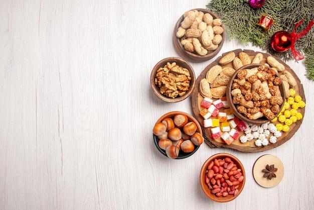 Vue de dessus de loin noix sur le plateau branches d'épinette avec différents bonbons et cacahuètes sur le plateau de la cuisine à côté des bols de noisettes noix sur la table