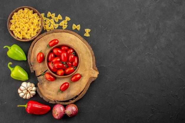 Vue de dessus de loin pâtes et tomates bol brun de tomates sur la planche de bois pâtes et oignon poivron et ail sur le côté gauche de la table