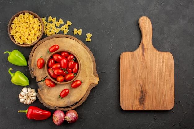 Vue de dessus de loin pâtes et tomates planche à découper bol brun de tomates sur la planche de bois pâtes et oignon poivron et ail sur la table