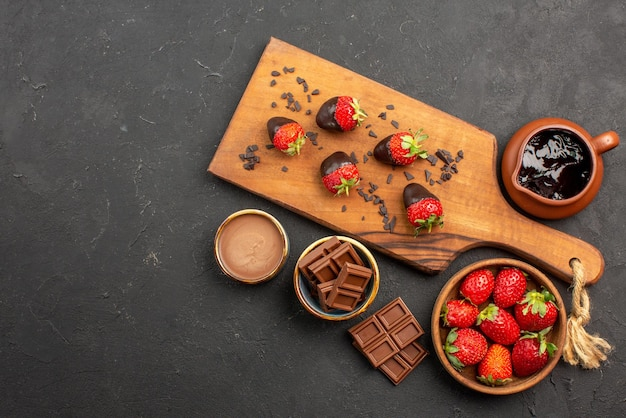 Vue de dessus de loin planche à découper fraises enrobées de chocolat sur une planche à découper à côté de la crème au chocolat et des fraises sur le côté droit de la table sombre