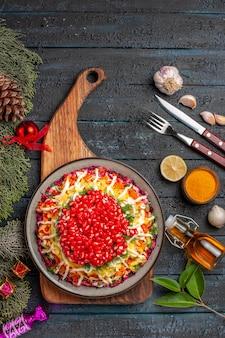 Vue de dessus de loin planche à découper plat de noël sur la planche à découper en bois à côté des bols d'épices couteau fourchette à l'ail et bouteille d'huile