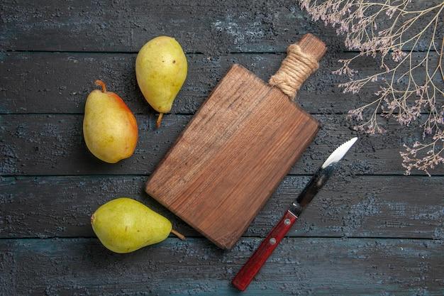 Vue de dessus de loin des poires et planche de trois poires à côté d'un couteau de planche à découper et de branches d'arbres
