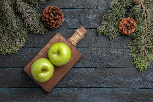 Vue de dessus de loin des pommes entre des cônes deux pommes vertes sur une planche à découper entre des branches d'arbres avec des cônes