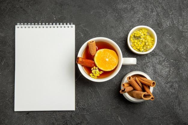 Vue de dessus de loin une tasse de thé avec un cahier blanc au citron à côté de la tasse de thé au citron et des bols de baies et de bâtons de cinabre au centre de la table