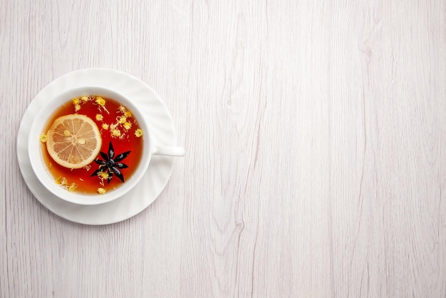 Vue de dessus de loin une tasse de thé sur la soucoupe une tasse de thé au citron sur la soucoupe sur le côté gauche de la table en bois