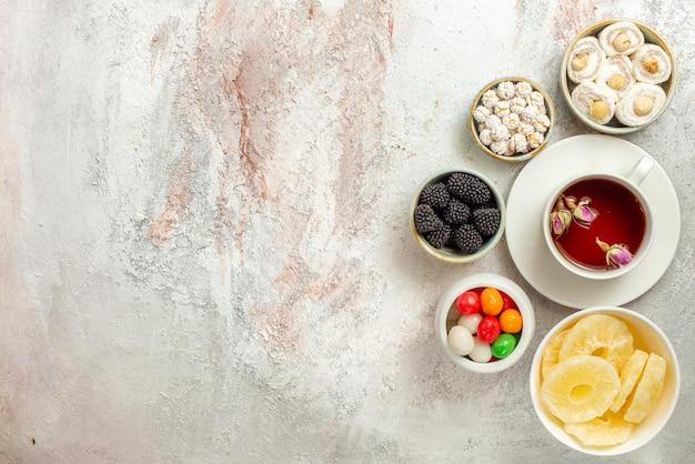 Vue de dessus de loin une tasse de thé une tasse de thé et des bols de différents bonbons ananas séchés délice turc sur fond blanc
