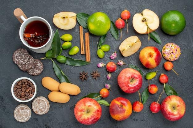 Vue de dessus de loin une tasse de thé une tasse de tisane bâtons de cannelle bonbons fruits et baies