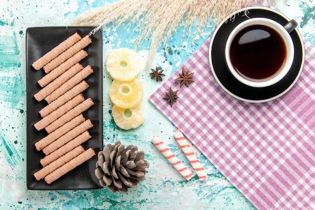 Vue de dessus de longs biscuits sucrés avec une tasse de thé et des anneaux d'ananas séchés sur le fond bleu