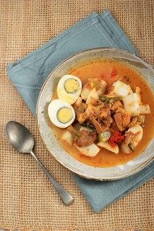 Vue de dessus lontong sayur padang, curry de légumes avec gâteau de riz pressé, servi avec œuf à la coque